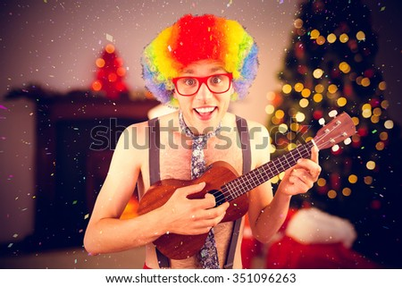 Geeky hipster in afro rainbow wig playing guitar against christmas tree with presents near the fireplace - stock photo