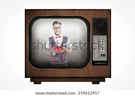 Geeky hipster offering christmas gift against retro tv - stock photo