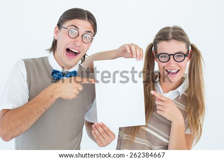 Geeky hipsters pointing at poster on white background - stock photo