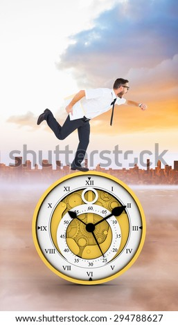 Geeky young businessman running late against city on the horizon - stock photo