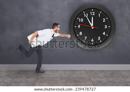 Geeky young businessman running late against grey room - stock photo