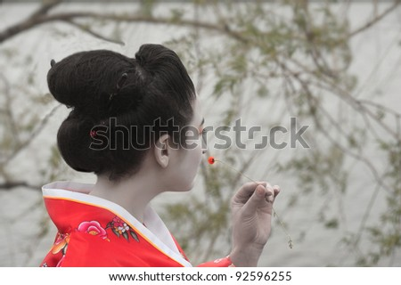Geisha with the little red flower - stock photo