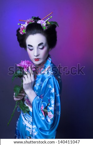 Geisha. Young woman in blue kimono and with flowers in her hair. - stock photo