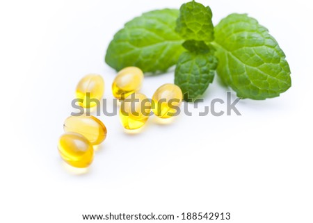 Gel vitamin capsules with mint leaf.  - stock photo