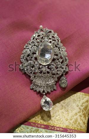 gems brooch on Thai silk fabric - stock photo