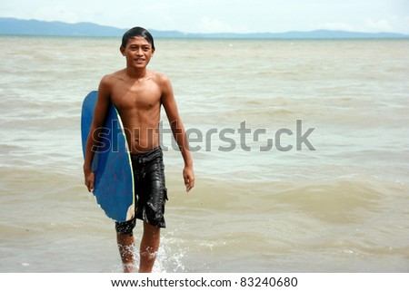GEN. SANTOS CITY, PHILIPPINES - AUG 20: Michael  Zamora 17 years old prepare for the skim board competition at  Gen. Santos City, Philippines on Aug. 20, 2011. Held annually for the city festival. - stock photo