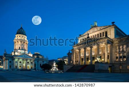 Gendarmenmarkt square in Berlin under a harvest Moon - stock photo