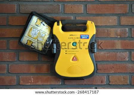 GENEMUIDEN, THE NETHERLANDS, 11 APRIL 2015 - Automatic External Defibrillator at a wall. - stock photo