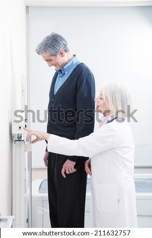 General practitioner measuring male patient's height in hospital. - stock photo