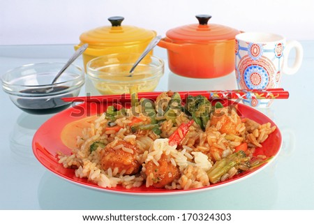 General Tso's Chicken in red plate reflecting in glass-top table in Chinese Restaurant. - stock photo