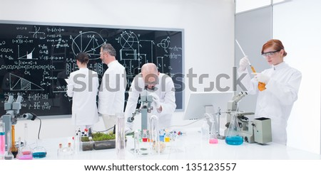 general view of four people in a chemistry lab conducting experiments and analyzing formulas on a blackboard on  the background - stock photo