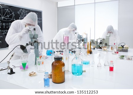 general-view of  three people observing and analysig chemical reactions in a lab  using colorful substances and lab tools  on a lab worktable with a blackboard on the background - stock photo