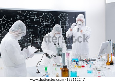 general-view of three scientists in a chemistry lab  manipulating lab tools, testing and using chemical techniques around a lab table with a blackboard on the background - stock photo