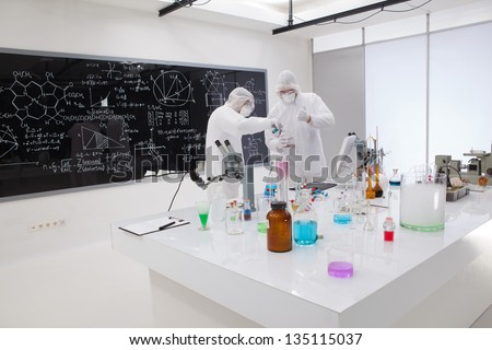 general view of two people making a laboratory experiment around a laboratory table with laboratory tools with colorful liquids and a blackboard with chemical formulas on the background - stock photo