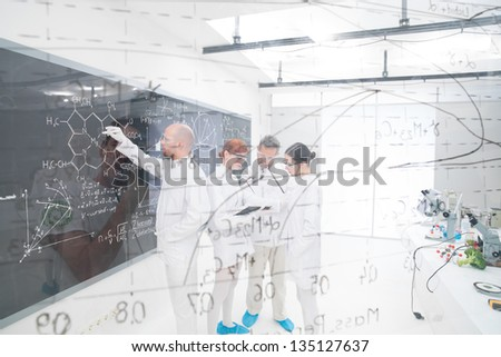 general-view seen trough a transparent board in a chemistry lab of people analyzing information - stock photo