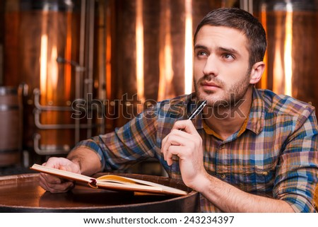 Generating ideas for his brewery. Thoughtful young man in casual shirt holding note pad and looking away while leaning at the wooden barrel with metal containers in the background   - stock photo