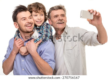 Generation portrait. Grandfather, father and son doing selfie, isolated a white background. - stock photo