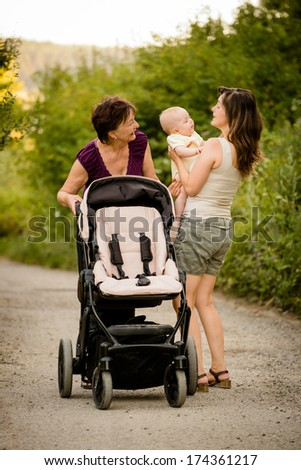 Generations - grandmother with her daughter and her granddaughter outdoor on walk with stroller - stock photo