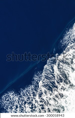 Generic background of a dark ocean surface with bow wave and slight motion blur. - stock photo