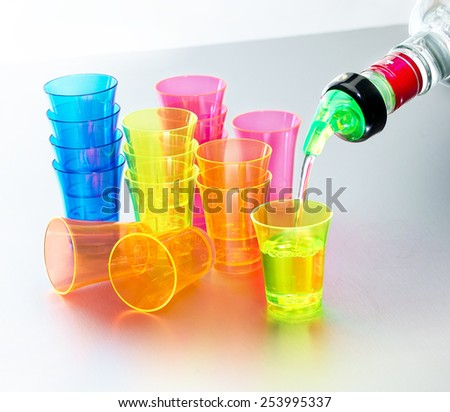 Generic colored shot glasses stacked on brushed metal surface with clear spirits vodka pouring from bottle through regulation measure spout  - stock photo