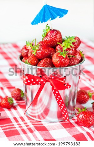 Generous crop of ripe fresh juicy gourmet red summer strawberry in decorative aluminium pail. Indoors close-up. - stock photo