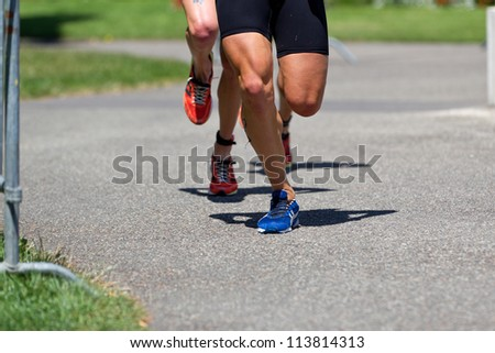GENEVA - JULY 22: Unidentified athletes competing in the running section of the 2012 ITU Triathlon European Cup, July 22, 2012 in Geneva, Switzerland - stock photo