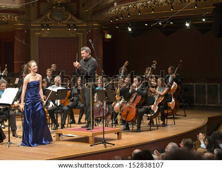 GENEVA - JUNE 23: Soloist violinist Alexandra Conunova Dumortier performs with the United Nations Orchestra conducted by Antoine Marguier at the Victoria Hall June 23, 2013 in Geneva, Switzerland. - stock photo