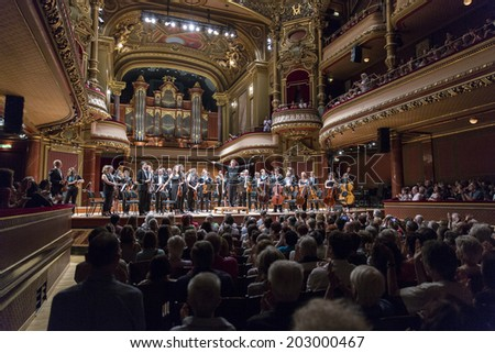 GENEVA, SWITZERLAND - JUNE 22, 2014: Conductor Antoine Marguier and the United Nations Orchestra take a bow at the Victoria Hall during a free concert as part of the city's festival of music. - stock photo