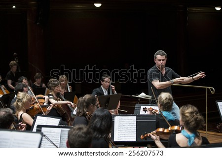GENEVA, SWITZERLAND - MARCH 21, 2014: Antoine Marguier conducts the UN Orchestra during rehearsals for the Spring Concert 2014 in the Victoria Hall.  - stock photo