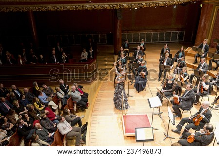 GENEVA, SWITZERLAND MARCH 20, 2013: Soloist violinist Solenne Paidaisi plays with the United Nations Orchestra conducted by Antoine Marguier at the Tchaikovsky Spring concert at the Victoria Hall. - stock photo