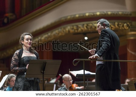 GENEVA, SWITZERLAND  MARCH 1, 2015: Soprano Eva Fiechter singing with the United Nations Orchestra at a concert at the Victoria Hall commemorating 200 years of Geneva in the Swiss Confederation. - stock photo