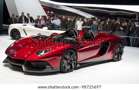 GENEVA SWITZERLAND - MARCH 12: The Lamborghini Stand displaying a full view of the lamborghini aventador convertible in RED, at the Geneva Motorshow on March 12th, 2012 in Geneva, Switzerland. - stock photo