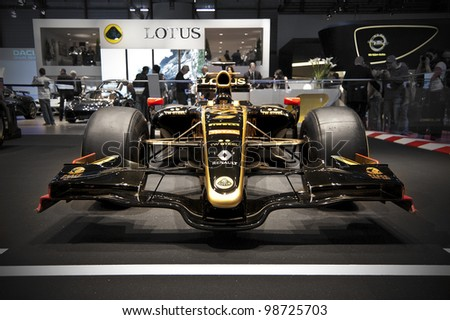 GENEVA SWITZERLAND - MARCH 12: The Lotus Stand displaying the 2011 Lotus Racing F1 Car, in John Player Special Colours, at the Geneva Motorshow on March 12th, 2012 in Geneva, Switzerland. - stock photo