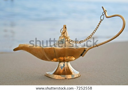 Genies lamp on seashore - stock photo