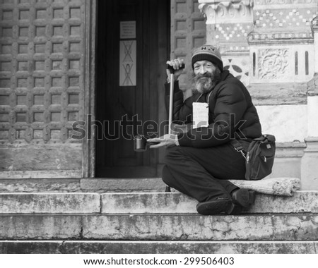 GENOA, ITALY - JANUARY 3: Homeless man begs for change outside of the San Lorenzo cathedral in Genoa, Italy on January 3, 2015.  - stock photo