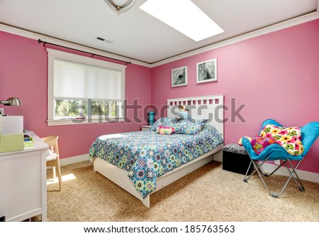 Gentle girls bedroom with white bed and pink walls. View of bed with blue bedding,blue chair - stock photo