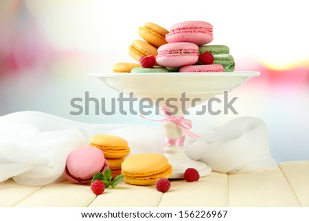 Gentle macaroons in vase on table on light background - stock photo