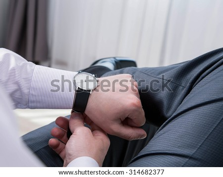 Gentleman clasping a wristlet and sitting in the room, closeup shot - stock photo