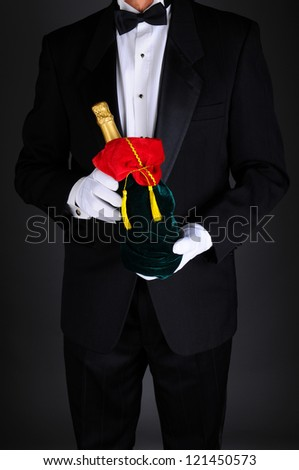 Gentleman wearing a tuxedo holding a champagne bottle wrapped up in a festive holiday gift bag. Man is unrecognizable on a light to dark gray background. - stock photo