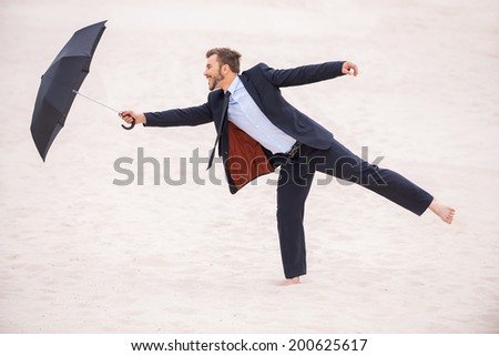 Gentleman with umbrella. Playful young man in formalwear holding umbrella while standing in desert  - stock photo
