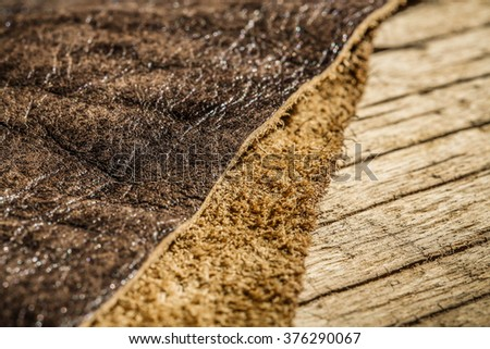 Genuine Leather and Suede, Brown. Macro, Close up Selective Focus. Wood Table. Concept and Idea of Fine Leather Crafting, Handmade Leather Handcrafted, Background Textured and Wallpaper. - stock photo
