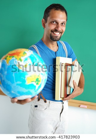 Geography teacher showing globe. Photo adult man with books and globe, creative concept with Back to school theme - stock photo