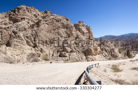 Geological rock formation with famous gravel dirt Ruta 40 - Route 40 - along the Andean Mountains with clear blue sky. - stock photo