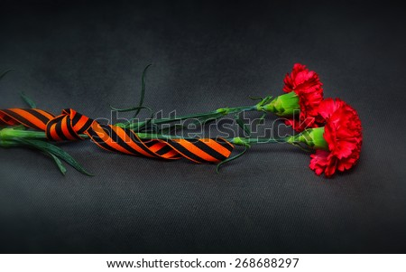 George Ribbon and flowers in memory of the victory in World War II. Victory Day on May 9th. - stock photo