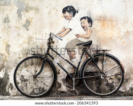 """George Town, Penang, Malaysia - April 23, 2014: """"Little Children on a Bicycle"""" street art mural by Lithuanian artist Ernest Zacharevic in Georgetown, Penang, Malaysia. - stock photo"""