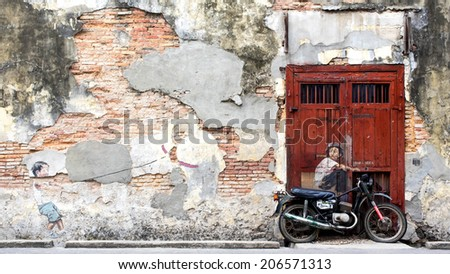 """Georgetown, Penang, Malaysia - April 23, 2014: """"Little Boy With Pet Dinosaur"""" and the iconic """"Boy on a Bike"""" street art mural by Lithuanian artist Ernest Zacharevic in George Town, Penang, Malaysia. - stock photo"""