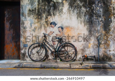 """Georgetown, Penang, Malaysia - February 19, 2015: """"Little Children on a Bicycle"""" street art on wall by Lithuanian artist Ernest Zacharevic in George Town, Penang, Malaysia. - stock photo"""