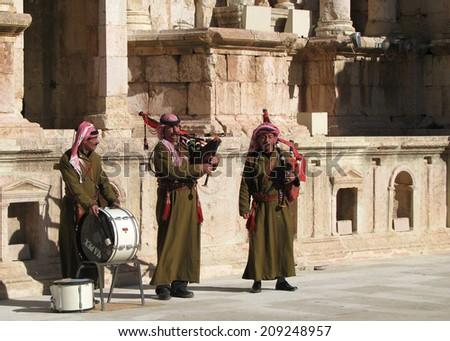 GERASH, JORDAN: Jan 21:  Jordanian musicians, including a bagpiper, perform in the Roman theater at the ancient ruins of Gerash on January 21, 2009. - stock photo