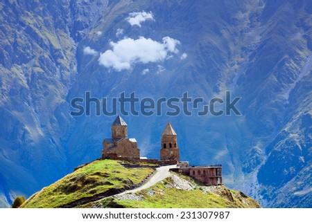 Gergeti christian church near Kazbegi, Stepancminda village in Georgia, Caucasus. - stock photo