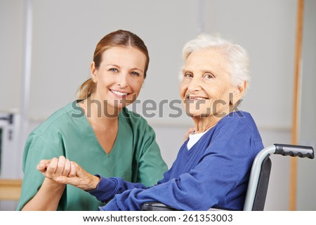 Geriatric care with nurse and happy senior woman in a wheelchair - stock photo